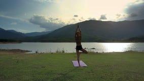 La muchacha de la opinión de la parte trasera se opone en actitud de la yoga en la estera al lago