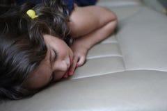 La muchacha de 3-4 a?os duerme en el asiento trasero del coche imágenes de archivo libres de regalías