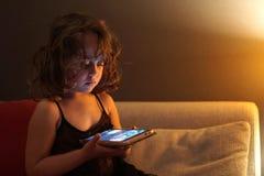 La muchacha de 3-4 a?os utiliza el tel?fono celular en la noche fotos de archivo libres de regalías