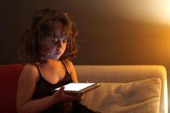La muchacha de 3-4 a?os utiliza el tel?fono celular en la noche imagenes de archivo