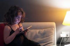 La muchacha de 3-4 a?os utiliza el tel?fono celular en la noche fotografía de archivo libre de regalías