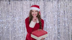 La muchacha de Papá Noel con un regalo en sus manos muestra su finger más reservado Fondo de Bokeh almacen de video