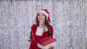 La muchacha de Papá Noel con un regalo en sus manos muestra su finger más reservado Fondo de Bokeh Cámara lenta almacen de metraje de vídeo