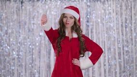 La muchacha de Papá Noel en traje muestra los pulgares abajo Fondo de Bokeh Cámara lenta metrajes