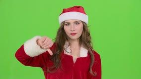 La muchacha de Papá Noel en traje muestra los pulgares abajo Pantalla verde Cierre para arriba Cámara lenta metrajes