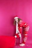La muchacha de Papá Noel está sosteniendo el bolso rojo grande de la Navidad Imagen de archivo libre de regalías