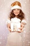 La muchacha de Papá Noel ofrece la caja de regalo Foto de archivo libre de regalías