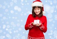La muchacha de Papá Noel que sostiene el regalo de la Navidad durante días de fiesta enciende el backgroun Imagen de archivo