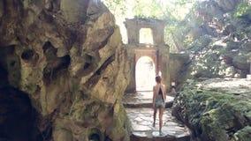 La muchacha de la parte trasera deja la cueva a través del arco de piedra contra luz metrajes