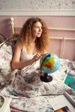 La muchacha de pelo largo en una camiseta blanca, sentándose en una cama Foto de archivo