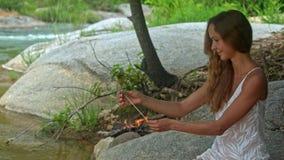 La muchacha de pelo largo fija el camarón en el palillo en la orilla del río almacen de metraje de vídeo