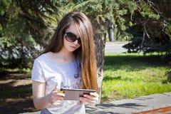 La muchacha de pelo largo goza de la tableta Fotografía de archivo libre de regalías