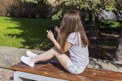 La muchacha de pelo largo goza de la tableta en banco Imágenes de archivo libres de regalías
