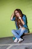 La muchacha de pelo largo hermosa con un smatrphone le gusta iphone cerca de a Foto de archivo