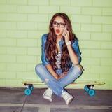 La muchacha de pelo largo hermosa con un smatrphone le gusta iphone cerca de a Foto de archivo libre de regalías