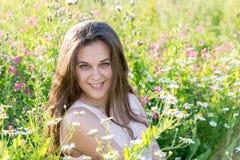 La muchacha de pelo largo hermosa en el claro con el prado florece Fotografía de archivo libre de regalías