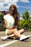 La muchacha de pelo largo hermosa en gafas de sol se sienta encendido foto de archivo