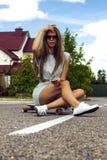La muchacha de pelo largo hermosa en gafas de sol se sienta encendido imagenes de archivo