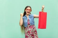La muchacha de pelo largo hermosa en ropa informal con los panieres, mirando la cámara, celebra la victoria Blondie caucásico Imagen de archivo libre de regalías