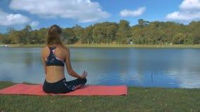 La muchacha de pelo largo se sienta en actitud de la yoga en el banco escarpado