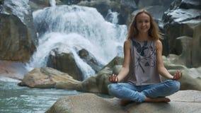 La muchacha de pelo largo sonriente hace yoga cerca de la cascada