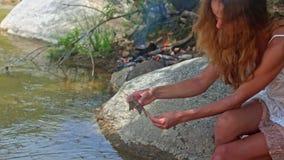 La muchacha de pelo largo de la vista lateral fija el camarón en el palillo en la orilla del río almacen de metraje de vídeo