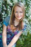 La muchacha de pelo rubio se sienta en un jardín Imagen de archivo