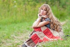 La muchacha de pensamiento se sienta en una hierba Imagenes de archivo