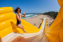 La muchacha de la playa salta la diapositiva de apogeo de los paseos Imágenes de archivo libres de regalías