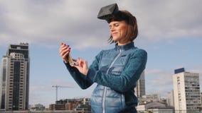 La muchacha de la realidad virtual utiliza la exhibición montada principal del vr al mandar un SMS a SMS o recibiendo llamada en  almacen de video
