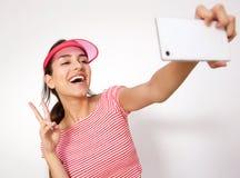 La muchacha de risa con paz da la muestra que toma el selfie Fotografía de archivo libre de regalías