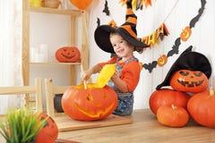 La muchacha de risa feliz del niño en un sombrero de las brujas cortó una calabaza para Hal Imagenes de archivo
