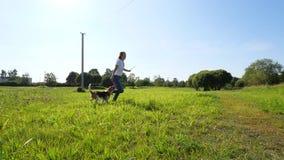 La muchacha de risa juega y corre con su perro del beagle almacen de video