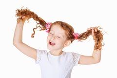 La muchacha de risa tira sus coletas hacia arriba a mano y canta la canción Imagenes de archivo