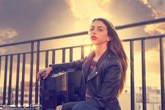 La muchacha de la roca del adolescente sienta al aire libre en la terraza del tejado Imagen de archivo libre de regalías