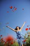 La muchacha de salto se está divirtiendo en un campo con las amapolas Fotografía de archivo