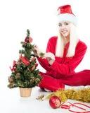 La muchacha de Santa adorna el árbol de navidad Fotos de archivo