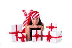 La muchacha de Santa está con un manojo de regalos. Imagenes de archivo