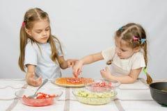 La muchacha de seis años observa y controla a su hermana más joven pone los ingredientes de la pizza Imagen de archivo