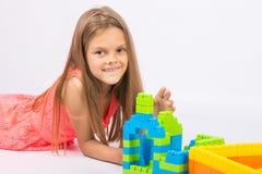 La muchacha de siete años construye una casa del diseñador del bloque Imágenes de archivo libres de regalías