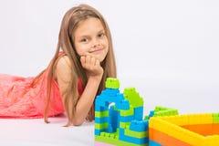 La muchacha de siete años construye una casa del diseñador del bloque y pensativo y diversión mira en el marco Foto de archivo