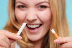 La muchacha de Smilling está rompiendo el cigarrillo Foto de archivo libre de regalías
