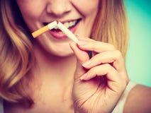 La muchacha de Smilling está rompiendo el cigarrillo Foto de archivo