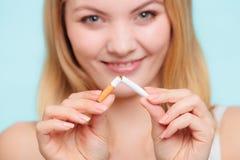La muchacha de Smilling está rompiendo el cigarrillo Imágenes de archivo libres de regalías