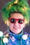 La muchacha de Splended con el pelo verde se vistió en guirnaldas de la Navidad Una muchacha está representando un árbol de navid Fotografía de archivo
