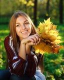 La muchacha de sueño que lleva a cabo un amarillo hojea Fotos de archivo libres de regalías