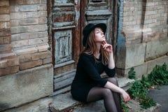 La muchacha de sueño rubia con el pelo largo, en vestido negro en sombrero, se está sentando en los pasos en el fondo de la antig imagenes de archivo