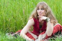 La muchacha de sueño se sienta en una hierba Imagen de archivo