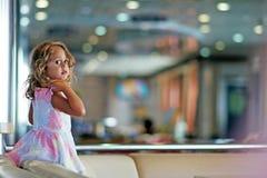 La muchacha de tres años con los ojos morados grandes juega feliz en el pasillo del transbordador que conecta Igoumenitsa con Bri imagenes de archivo