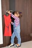 La muchacha de tres años saca del tirador de puerta un vestido rojo hermoso en una suspensión Imagen de archivo libre de regalías